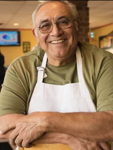 Older smiling caucasian male green shirt and white apron