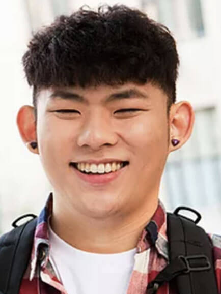 Smiling young Asian male with dark hair, wearing plaid shirt over t-shirt and backpack