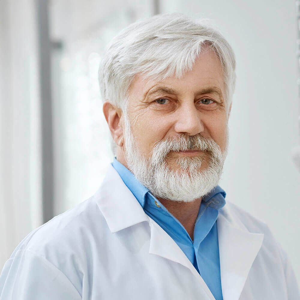 Older caucasian male with white hair, blue shirt and white lab coat